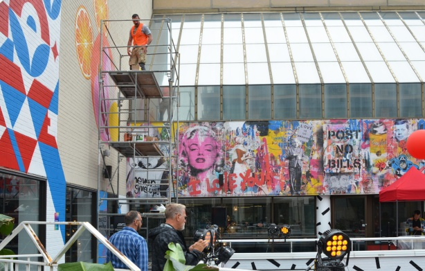 a man in an orange vest is up on scaffolding as he paints a mural, two other men are looking at finished murals