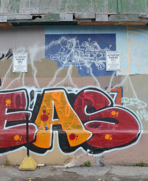 blue and white blueprint graffiti with large red and yellow text scrawl below it, on a wall in an alley