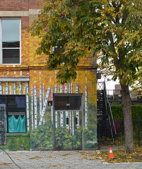 a tree in front of a building with painting of birch trees in autumn on it, including on the door and around the windows