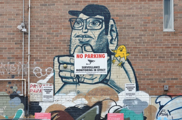 an old uber5000 painting on a wall of a man in black baseball cap and glasses with a little yellow birdie on his shoulder, a no parking sign on top of man's hands