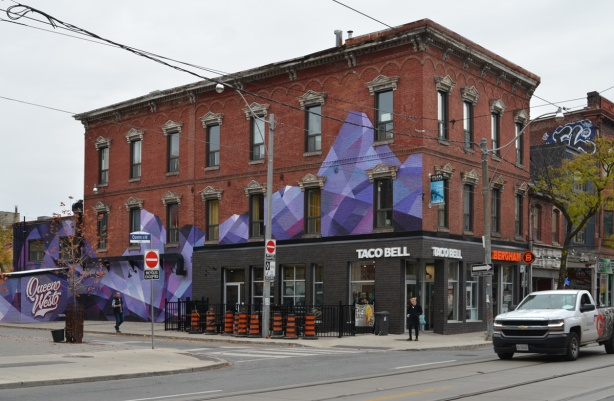 view from across the street, purple and black abstract street art mural on exterior of building at Queen West and Denison, old three storey brick building