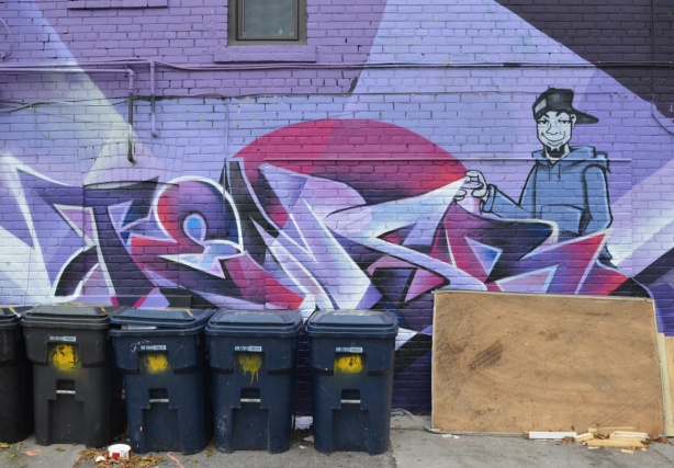 garbage bins, blue bins, in front of a purple wall with text street art and a painting of a young man with a can of spray paint
