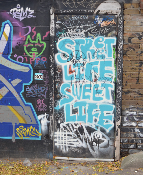 graffiti covered door with turquoise painted words that say street life sweet life
