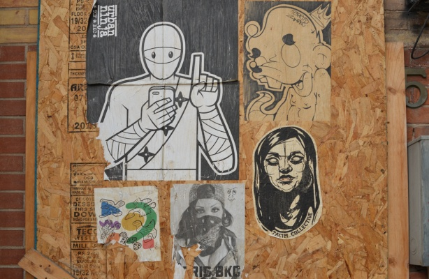 paper paste ups on plywood covering a window