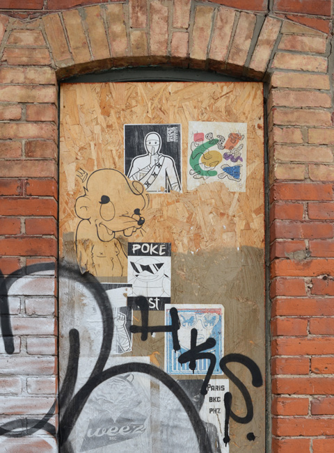 paper paste ups on plywood covering a door