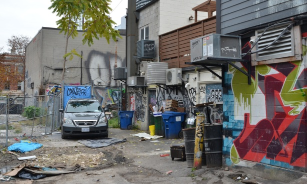 messy alley with car parked, trash bins, barrels, graffiti, air conditioners, back walls,