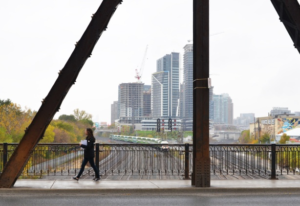 a woman walks over the bridge on Bathurst over the train tracks, GO train going westward in the background, as well as taller buildings to the west