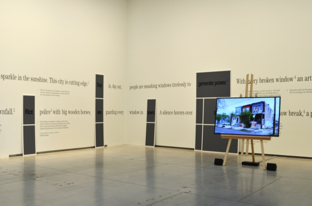 room at the Art Gallery of Ontario with words written around the walls, and a flat screen TV laying a video in the middle of the room