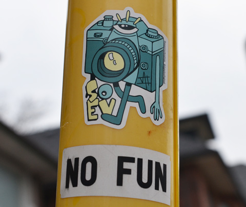 sticker on a yellow pole, camera with legs and arms, also a sticker below it that says no fun