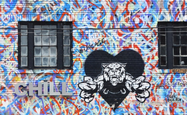 part of the front of a building that has been painted in red, white, blue, and purple squiggles, with a black heart and a roaring tiger leaping out of the heart, also the word Chill in silver block letters