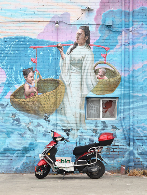 a black and red motorbike is parked by a mural in Chinatown of a person carrying babies in baskets.