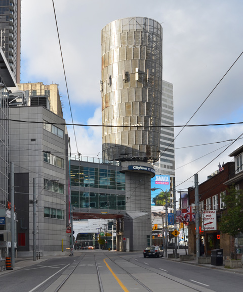 looking west on Dundas Street towards Victoria Street, large cylinder structure above the street at City News building, TTC streetcar turn with walkway above it, billboards of Yonge Dundas square behind it