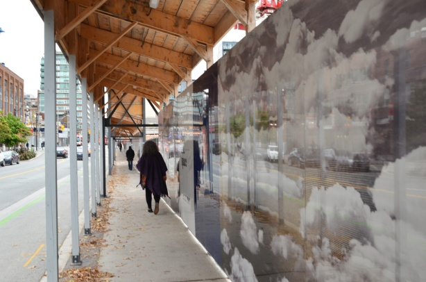 a woman walks past hoardings on Sherbourne street that are shiny and have pictures of clouds on them