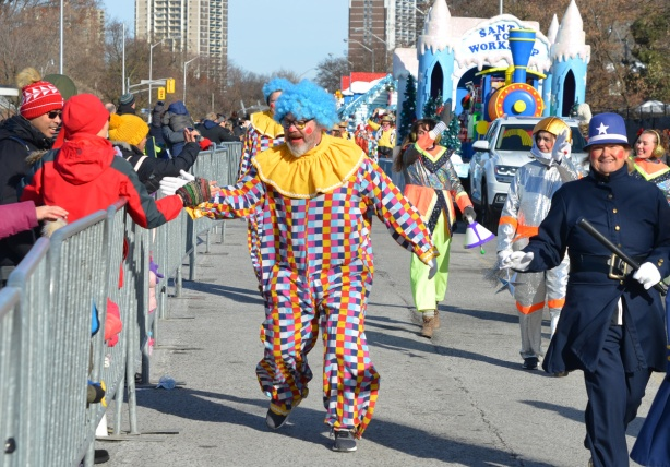 clowns in blue wigs and chequered clothing greet spectators at parade as they walk past