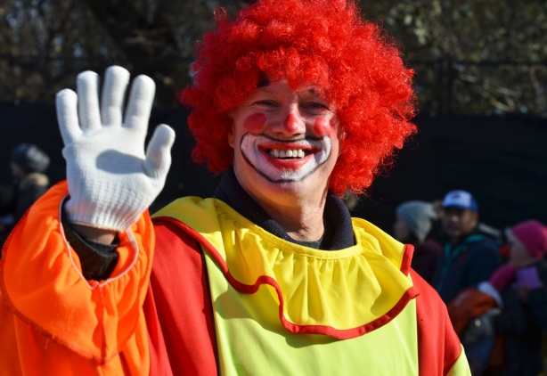 Santa Claus parade, clown waving, white gloves, red fuzzy wig