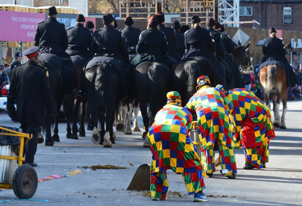 clowns in primary colours, big squares on fabric in clothing, with shovels in hand cleaning the street after the police horses go by
