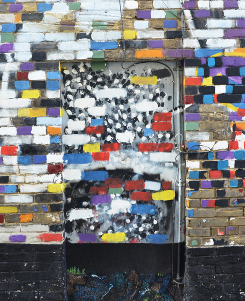 a brick wall where the bricks have been painted different colours like a giant mosaic, windows, and doors in that wall are also painted, in an alley,