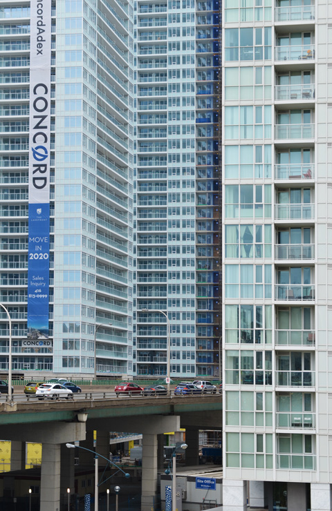 two tall glass tower condo buildings with the Gardiner Expressway, an elevated road, passes between the two of them, cars on the road