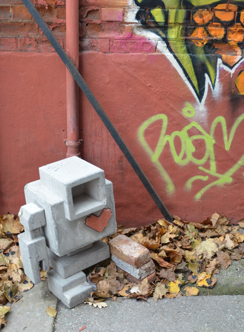 an old concrete lovebot with an arm and a leg missing. on two bricks instead of the leg, in a pile of leaves, beside a rust coloured wall
