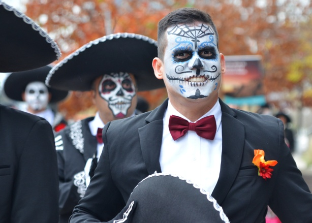 two men in white face day of the dead decorated, one with sombrero on and the other with the hat in his hand, wearing black suits, white shirts, and red bowties