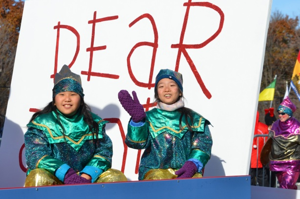 two girls dressed as Santa's elves sit on a parade float in front of a large white sign with red letters that says dear santa