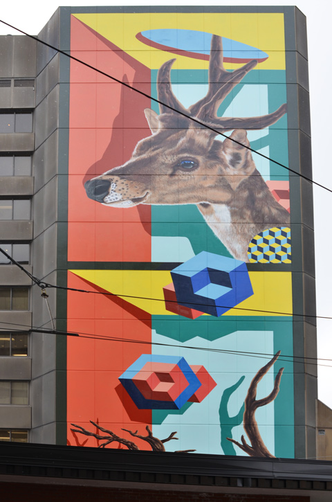 large mural by birdo, vertical, on the side of a building, with a realistic deer head at the top