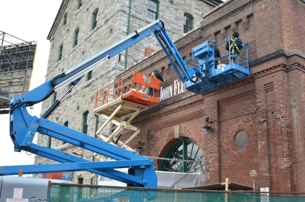 men on a blue lift crane at the distillery district, old brick building
