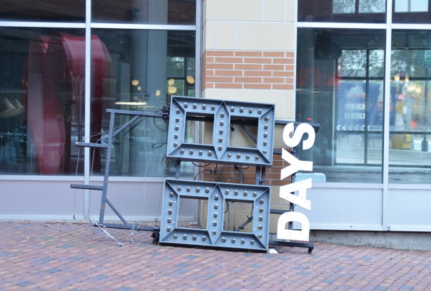 leaning against the side of a building, on its side on the ground, the sign at the distillery district that says how many days left until Christmas