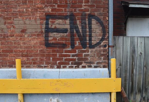 large black letters make the word end on a red brick wall