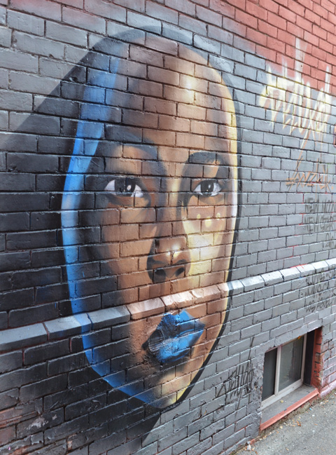 a large woman's face painted on the side of a brick building