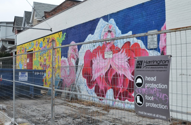 chain link construction fence in front of a mural of dancing pink flamingoes