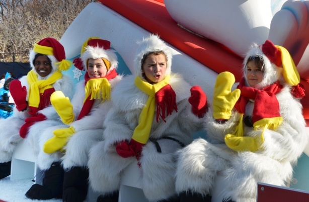 four kids sitting on a parade float dressed as white fuzzy bears with yellow scarves and red mitts