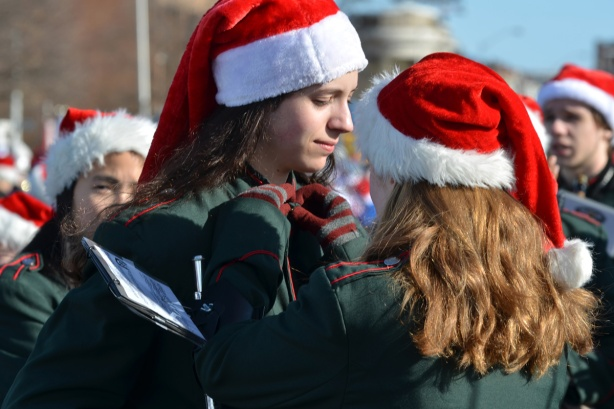 two members of a band, one woman is helping the other with a button on her uniform, both are wearing Santa hats, start of Santa Claus parade