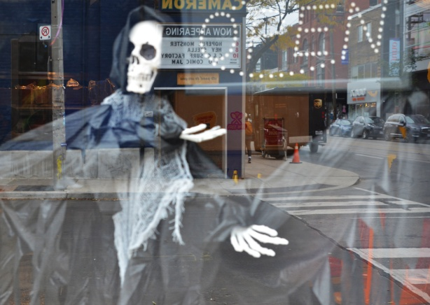 a skeleton wrapped in black hood and cape in a window, with reflections of stores and street on Queen West