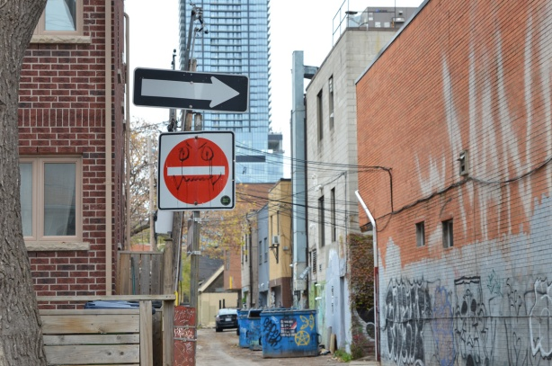 at the entrance to an alley, a red and white do not enter sign has been altered, a face has been drawn it in black sharpie