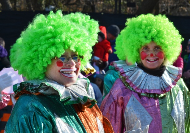 two clowns in Santa Claus parade with red nose and curly green hair, shiny clothing
