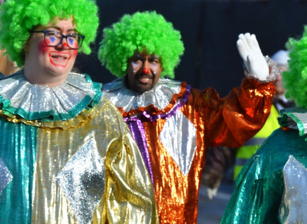 two clowns in Santa Claus parade with red nose and curly green hair, shiny clothing, one is waving at the camera with a white gloved hand