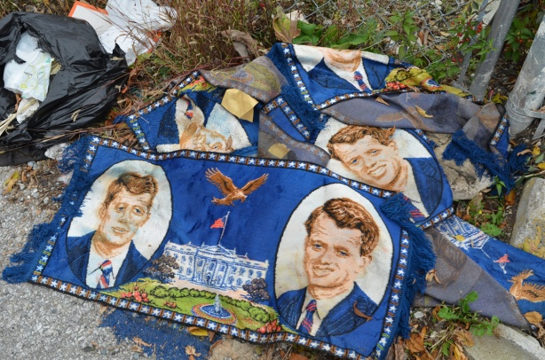 small blue carpets in a pile on the ground, about 4 of them, with pictures of John F Kennedy and Bobby Kennedy, a brown eagle, and some words
