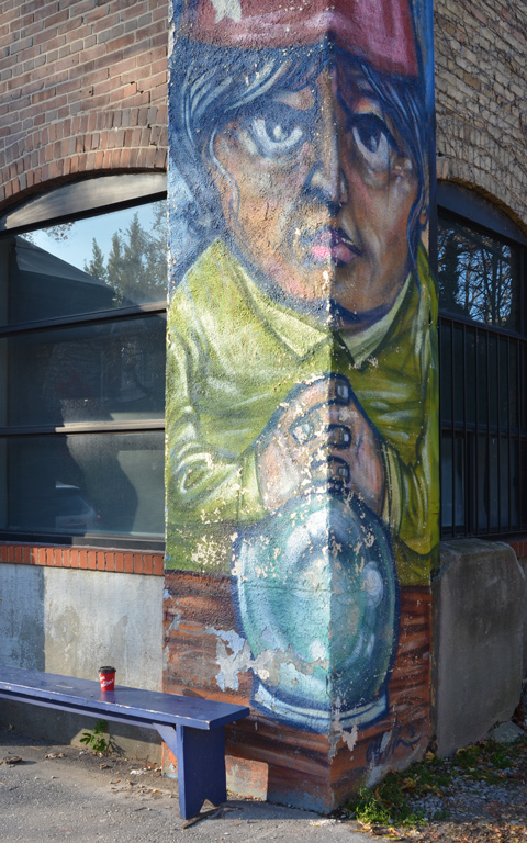 a painting of a man with hands folded in front, and wizard cap on, on the exterior corner of a building