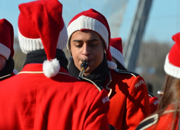 a young man from Malvern High School band is warming up before the Santa Claus parade