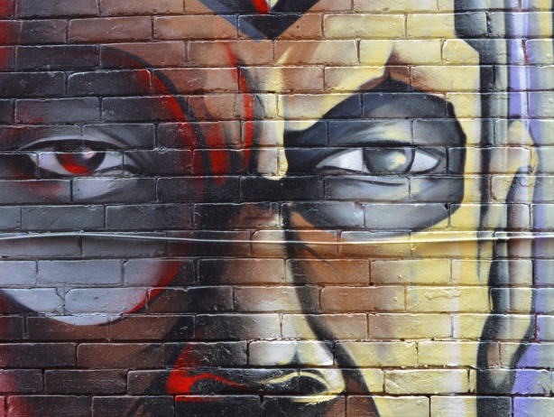 part of mural of man's face, two eyes and a nose,