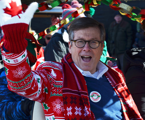 Toronto mayor John Tory wearing a Christmas sweater and red and white Canada mitts, waves at the start of the Santa Claus parade