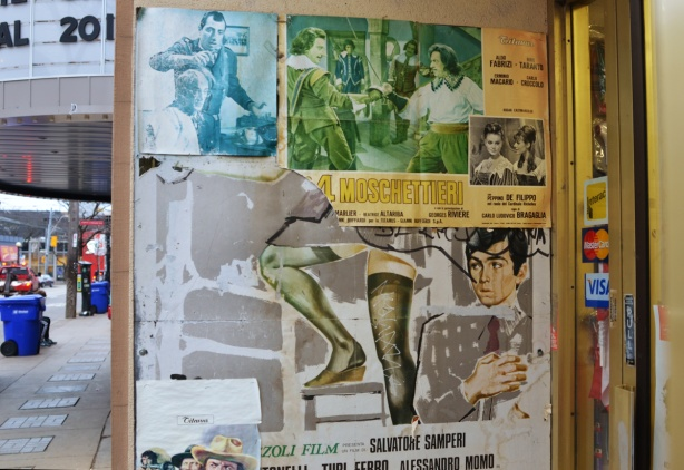 wall in a doorway with old posters for Italian movies, some on top of others