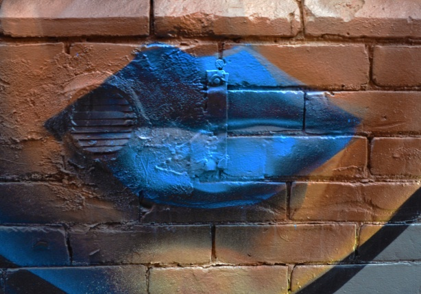close up of a pair of blue lips painted as part of a mural of a woman's face