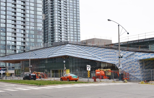 construction of new Canoe Landing Centre on Fort York Blvd, low rise building with sloping roof, tall condo in the background