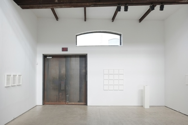 walls of a gallery, white, with some all white artwork on the walls, also a large old double door that is the exit