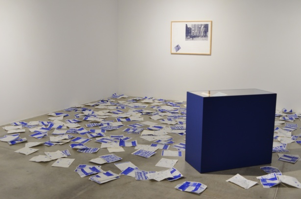 blue and white papers strewn over the floor, discarded, with a framed picture on the wall, and a blue desk in the middle