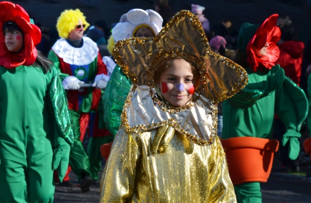 young woman walking in Santa Claus parade with large gold star shaped head-dress on, gold costume, other people dressed as plants in flower pots are nearby