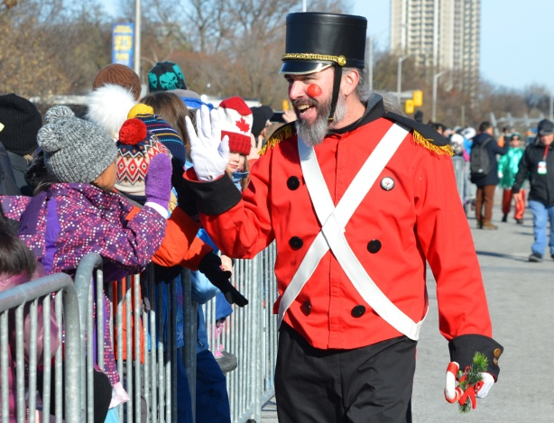 man dressed as a toy soldier in red jacket, white leather straps, black hat and black pants, in Santa Claus parade, greets people in the crowd as he walks