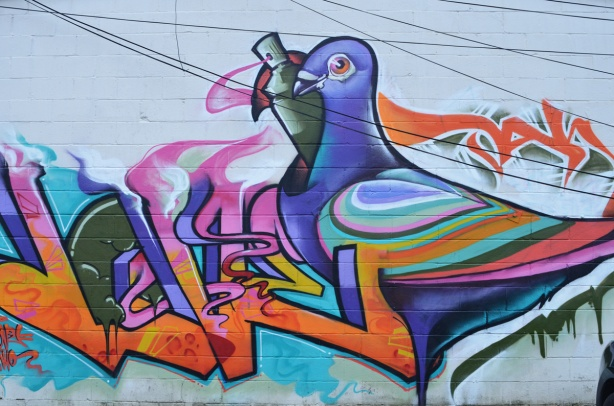 a stylized pigeon, painted on the side of a building, with a spray paint can by it's head